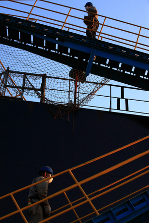 shipbuilder: Two workers going up some stairs in a shipyard