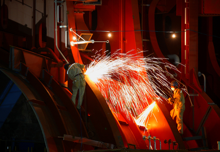 shipbuilder: Two workers welding parts at the hull Editorial