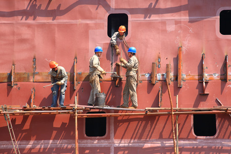 shipbuilder: Workers working on a constructing vessel