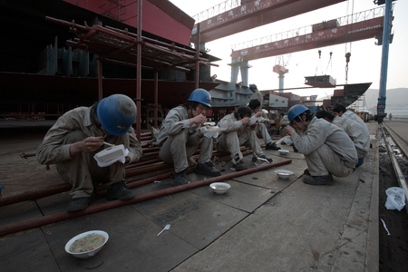 shipbuilder: Workers eating while resting at a dock