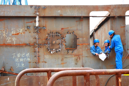 shipbuilder: Three workers on a constructing vessel