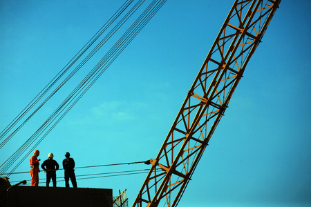 shipbuilder: Three construction workers standing on a building