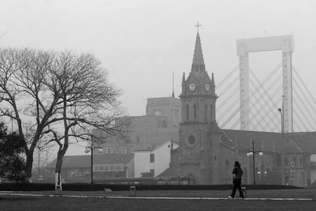 30 34 years: Woman walking in front of a catholic church