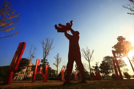 parentage: Silhouette parent and child decorations at a park
