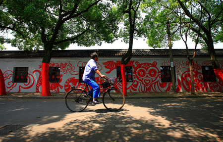 cuttings: Man cycling pass a building with chinese paper cuttings