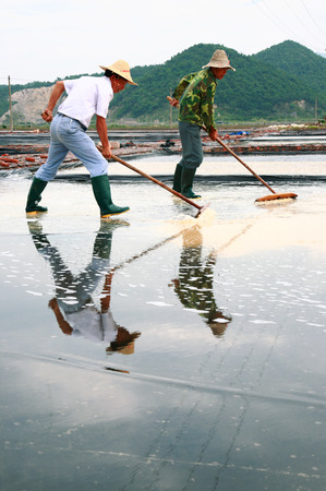 evaporation: Man working in a salt evaporation pond Editorial