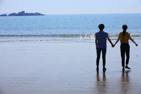 two people only: A couple holding hands by the beach Editorial