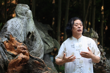 wood carvings: Zhang DeHe (root carving master) explaining about wood carvings