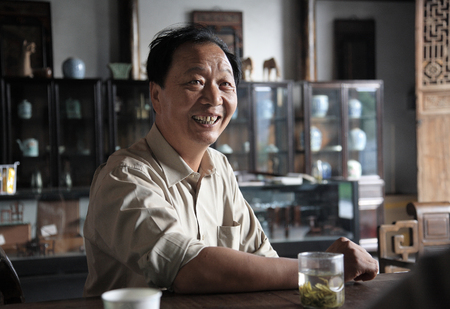 curator: A man smiling while having a Chinese tea