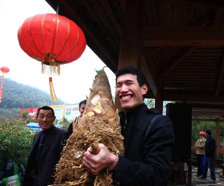 turismo ecologico: Hombre que sostiene un brote de bambú en el sexto municipio Hengjie festival de turismo de ocio ecológico