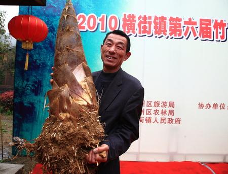 turismo ecologico: Hombre que sostiene un brote de bambú en el escenario en Hengjie sexto municipio festival de turismo de ocio ecológico Editorial