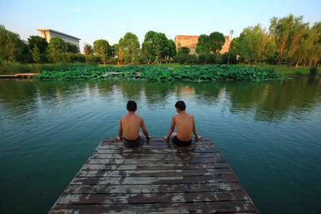 boys only: Two boys sitting at a dock in Yinzhou park