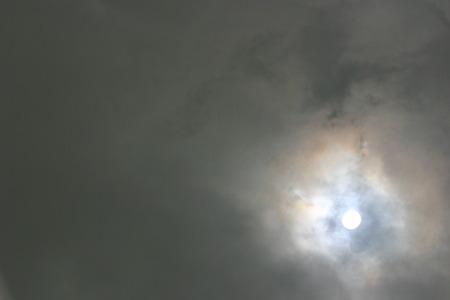 enveloped: Sun enveloped by dark clouds Stock Photo