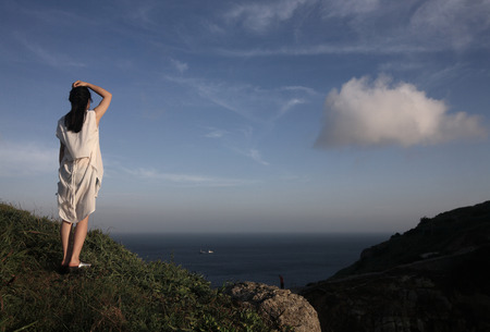 one person only: Woman standing by the cliff Stock Photo