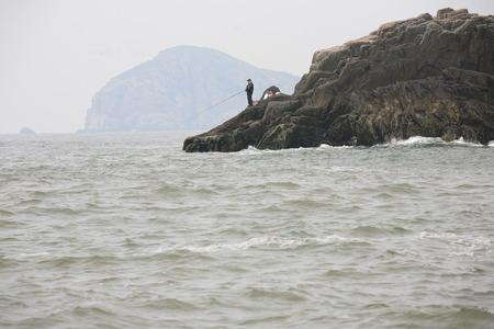 hombre pescando: Pesca del hombre por el acantilado