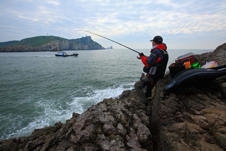 man fishing: Pesca del hombre por el acantilado