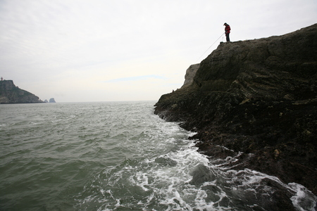 sea cliff: Man fishing by the cliff