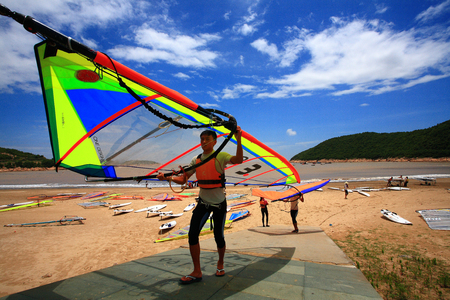 sailboard: Windsurfers carrying a sail at the beach
