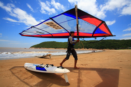 sailboard: Man carrying a sail at the beach