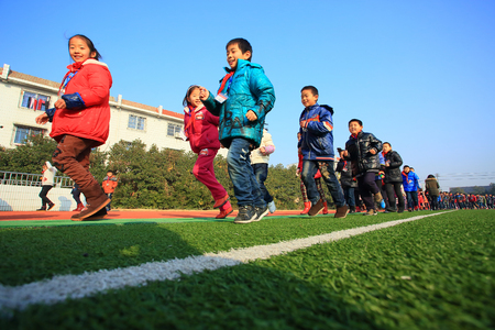 12 13 years: School children running around the field