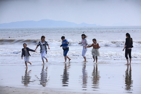 10 11 years: Mother and children having fun by the beach