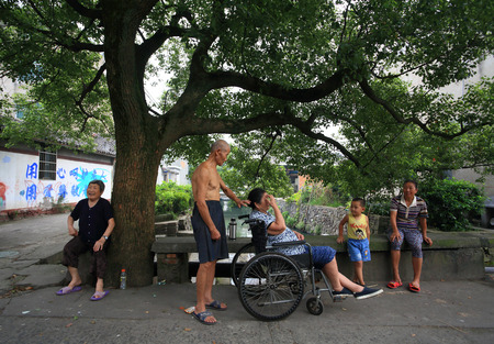 under a tree: Villagers enjoy the shade under a tree Editorial