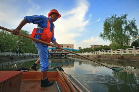maintaining: Man maintaining cleanliness of the river