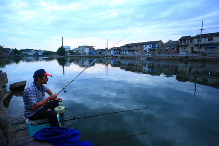 one mature man only: A local angler fishing by the river at dawn