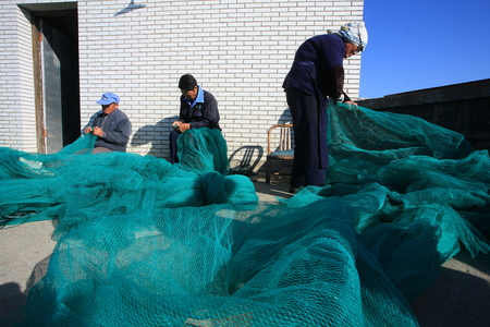 only three people: Men mending their fishing nets Editorial