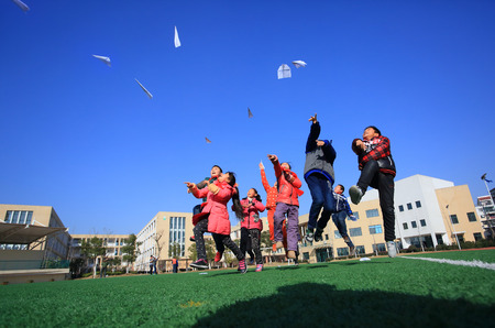 paper airplane: Students playing paper airplane in the field