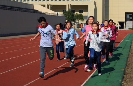 12 13 years: Girls running in Gulin town middle school running track