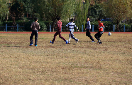 12 13: Boys playing football in the Gulin middle town school field