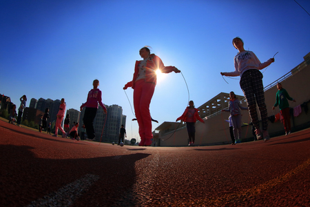 13 14 years: Low angle view of girls skipping rope on Gulin town middle schools running track Editorial