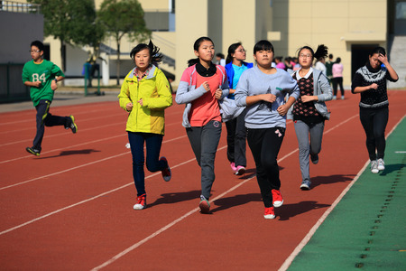 12 13: Close up on students running in Gulin town middle school running track Editorial