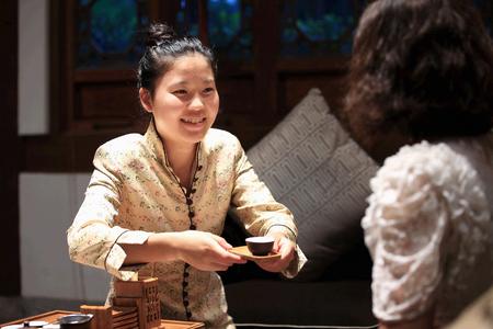 respecting: Woman serving tea in Huacheng New Century Resort Editorial
