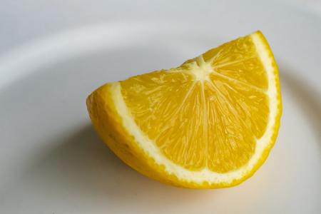 close up lemon slice on white plate