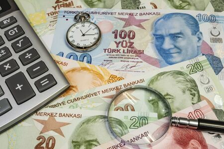close up turkish lira banknotes with clock, magnifier and calculator