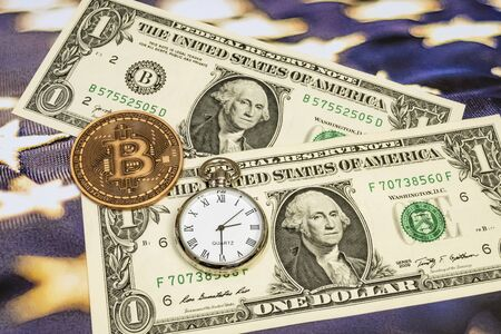 Bitcoin is an innovative payment network and a new type of currency. close up bitcoin coin on background with US dollars and clock.