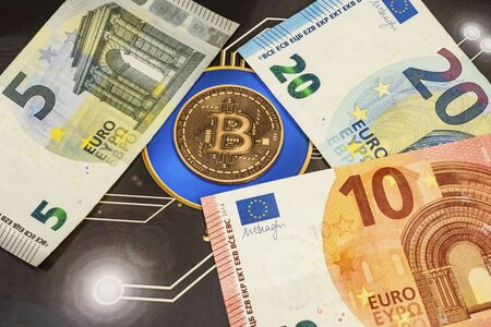 close up bitcoin coin with euro banknotes and magnifying glass on background.