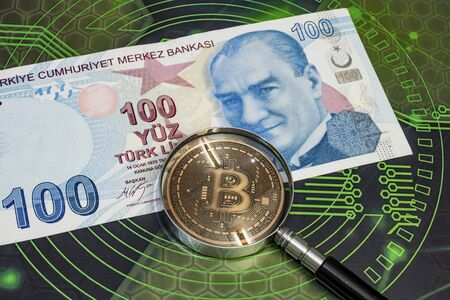 close up bitcoin coin and magnifying glass with turkish lira banknotes on background