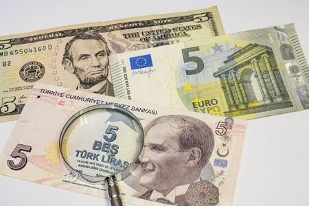 close up american dollar, turkish lira and euro banknotes with magnifying glass on white background