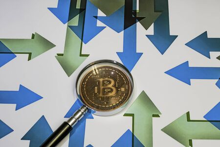 close up bitcoin coin with magnifying glass  on background