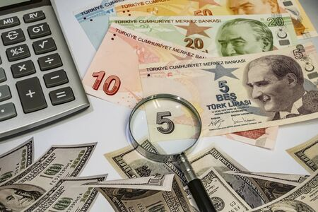 close up turkish lira banknotes with calculator and magnifier on background