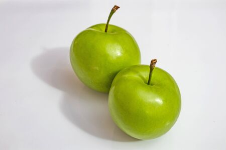 close up green plums on white background
