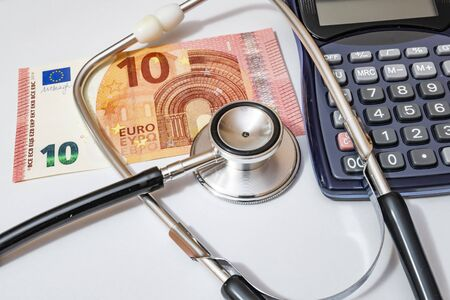 close up currency paper banknote on white background with stethoscope and calculator.