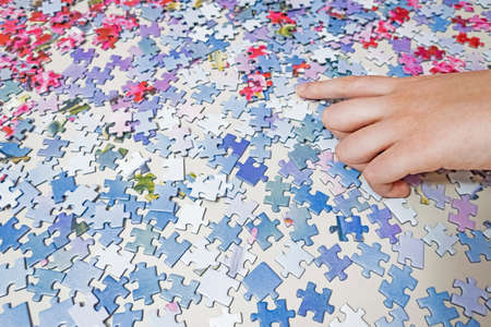 close up hand holding puzzle pieces Stok Fotoğraf