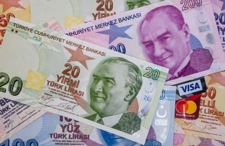 istanbul,turkey january 27,2021.close up visa and mastercard credit cards with Turkish lira banknotes. Banco de Imagens - 163757195