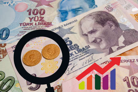 close up turkish gold coin with magnifying glass and chart on turkish lira banknotes Banco de Imagens