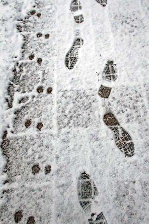 A snowy road and footprints in winter Banco de Imagens - 164420606