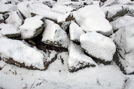 rocks and snow on the sea shore in winter
